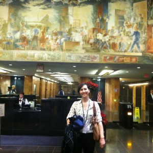 Beth Gawne standing in front of mural on the wall of the State Department