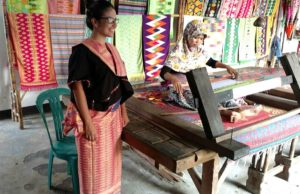 Visit to women's traditional hand weaving cooperative, Patuh Cooperative, during field site visit in island of Lombok, Indonesia; wearing a traditional wedding dress